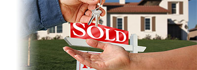 one person handing keys to home with sold sign