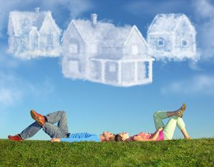 couple lying on grass looking at clouds shaped as houses