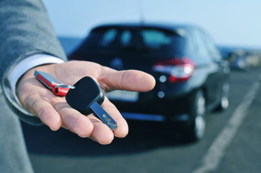 closeup of person holding keys in front of a car